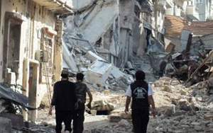 Photo detail: Free Syrian Army fighters walk through rubble of Homs, Syria.
