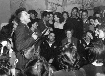 Image: Peter Seeger sings, 1944. Eleanor Roosevelt smiles, sitting between 2 servicemen. Photo by: Joseph A. Horne/Library of Congress