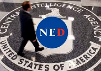 Image: Man walks across NED logo super-imposed on CIA logo.